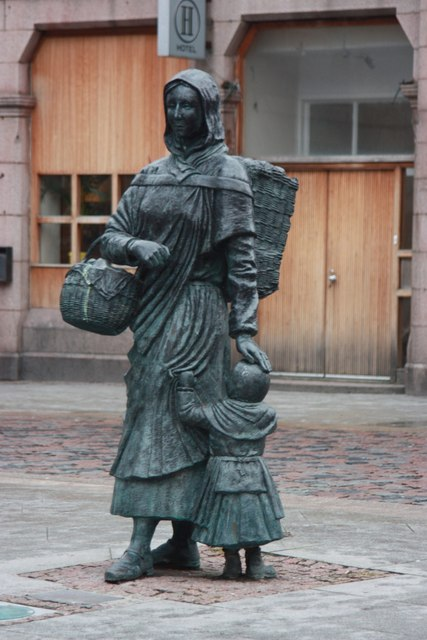 Photograph of the Fisher Jessie statue in Peterhead, Scotland. (A naturalistic bronze cast statue of a fish-wife and little girl, the woman carrying a creel and a basket.)